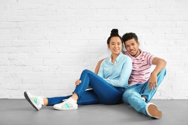 Gelukkig paar tussen verschillende rassen zittend op de vloer in een lege ruimte. verhuizen naar nieuw huis