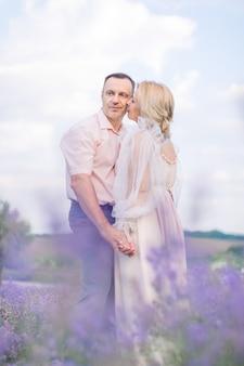 Gelukkig paar van middelbare leeftijd, omarmen en genieten van romantische momenten samen in het lavendelveld