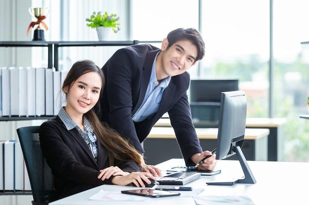 Gelukkig paar van onderneemster en zakenmanpartners die positieve volwassen zaken bespreken die met computer aan houten lijst en ideeën op vergadering in bureau samenwerken.