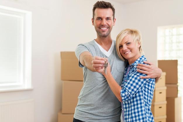 Gelukkig paar verliefd op sleutel tot nieuw huis
