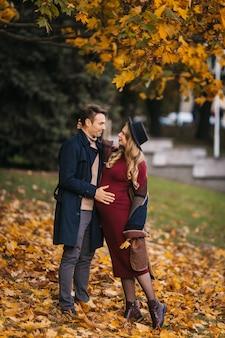 Gelukkig paar wandelen in het park met gele bladeren op de herfstdag knappe man en mooie pre...