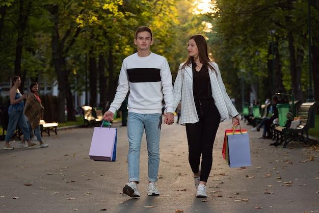 Gelukkig paar wandelen in het park met kleurrijke boodschappentassen met souvenirs. jonge man en vrouw lopen samen.