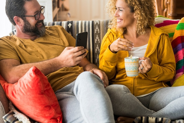 Gelukkig paar zittend op de bank en kijken naar elkaar terwijl ze koffie drinken en thuis mobiele telefoon gebruiken. verliefde paar vrije tijd samen doorbrengen thuis. paar dat van aangezicht tot aangezicht kijkt.