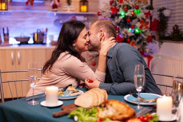 Gelukkig paar zoenen in kerstkeuken na huwelijksaanzoek
