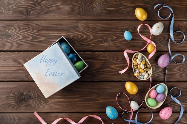 Gelukkig paaskaart. geschenkdoos met paaseieren. chocolade en gekleurde paaseieren met de bogen van het kleurenlint op houten achtergrond.