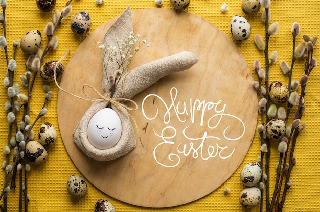 Gelukkig paaskaart. leuk ei in een servet in de vorm van een konijn op een keramische plaat. kwarteleitjes. willow twijgen. vrolijk pasen-concept