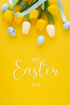 Gelukkig pasen achtergrond met eieren en tulpen en belettering