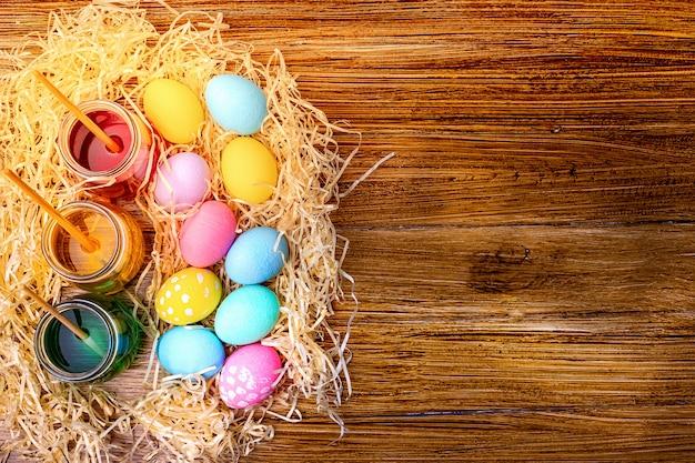 Gelukkig pasen. achtergrond met kleurrijke eieren in stro. tafel versieren voor vakantie. bovenaanzicht