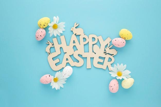 Gelukkig pasen-bord met eieren en madeliefjes op een blauwe achtergrond