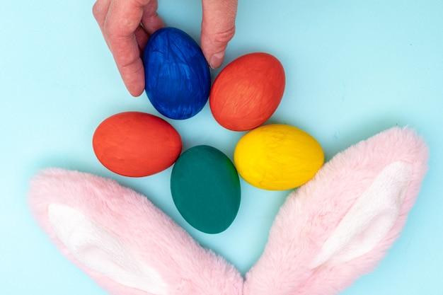 Gelukkig pasen-concept. hand legt beschilderde paaseieren en roze konijnenoren op een blauwe achtergrond. geef gekleurde eieren voor pasen.