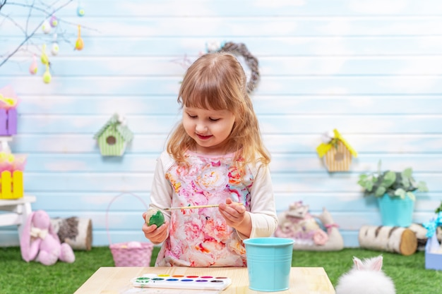 Gelukkig pasen! een schattig klein meisje schildert een paasei met een penseel.