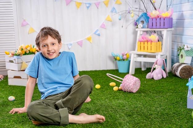Gelukkig pasen! een vrolijk verrast jongen met blote voeten zit op het gras