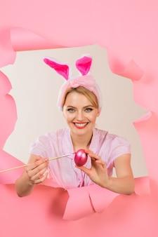 Gelukkig pasen. eierenjacht. vrouw die met konijntjesoren eieren schildert. paasdag concept.
