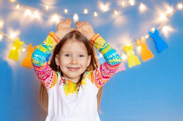 Gelukkig pasen! grappig kindmeisje met konijntjesoren en eieren op een blauwe achtergrond