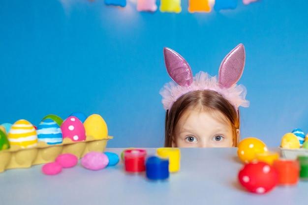 Gelukkig pasen! grappig kindmeisje met konijntjesoren en eieren thuis in de keuken