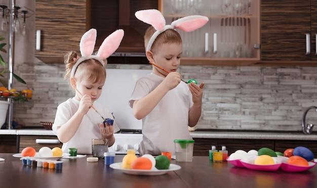 Gelukkig pasen. grappige en gelukkige kinderen, een jongen en een meisje met konijnenoren spelen, bereiden zich voor op de vakantie en schilderen eieren.