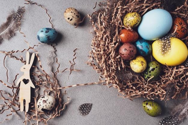 Gelukkig pasen. heldere felicitatie pasen achtergrond. bovenaanzicht, plat gelegd. kleurrijke paaseieren, konijn en veren in een nest op een grijze achtergrond, close-up. traditionele retro-stijl.