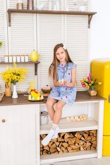 Gelukkig pasen. het kind maakt zich op voor pasen. een meisje zit in een ingerichte keuken en houdt gekleurde paaseieren vast.