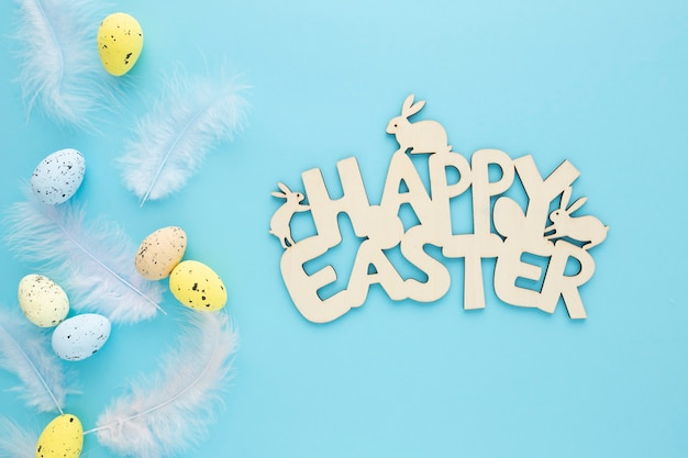Gelukkig pasen houten bord met eieren op een blauwe achtergrond