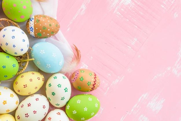 Gelukkig pasen! kleurrijk van paaseieren in nest op roze houten achtergrond.