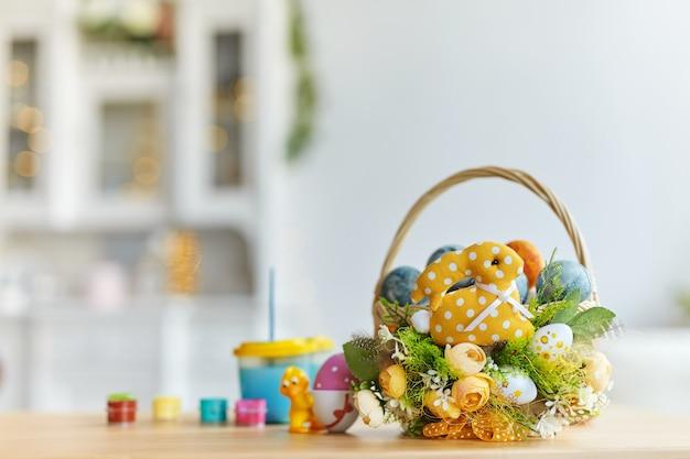 Gelukkig pasen. kleurrijke eieren in ingerichte mand. gekleurd tafel, verf en borstels
