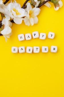 Gelukkig pasen. kubussen met tekst op gele achtergrond. lente brunches met witte bloemen. minimalistische platte lay.