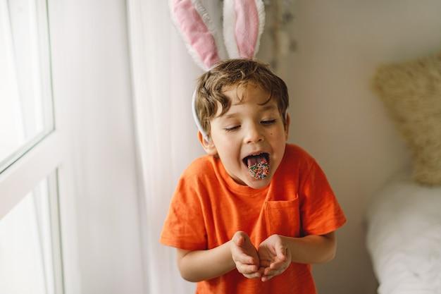 Gelukkig pasen. leuke jongen eet en speelt met hagelslag van pasen.