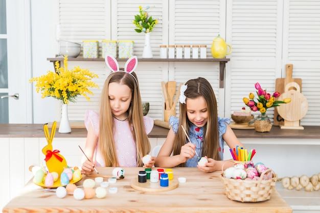 Gelukkig pasen. leuke meisjes met oren van konijnen schilderen eieren.