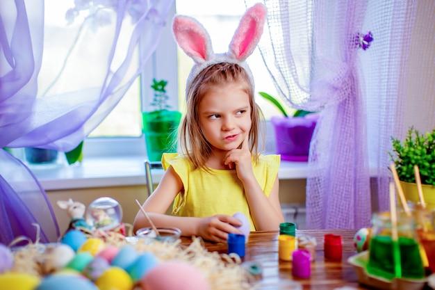 Gelukkig pasen-meisje die in konijntjesoren eieren, klein kind thuis schilderen. lente vakantie