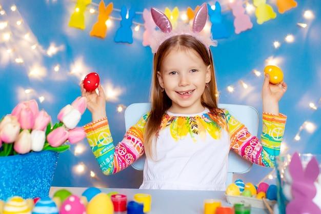 Gelukkig pasen! meisjes met konijnenoren schilderen eieren.