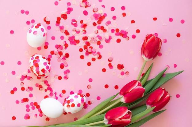 Gelukkig pasen. paaseieren versierd met papieren confetti en tulpen