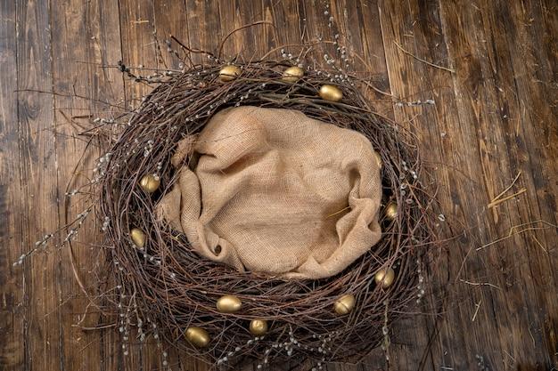Gelukkig pasen! pasen decoratie. een nest van wilgentakken met gouden eieren
