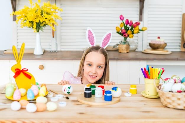 Gelukkig pasen. portret van een meisje met konijnenoren op een achtergrond van beschilderde eieren. een gelukkig kind bereidt zich voor op pasen.