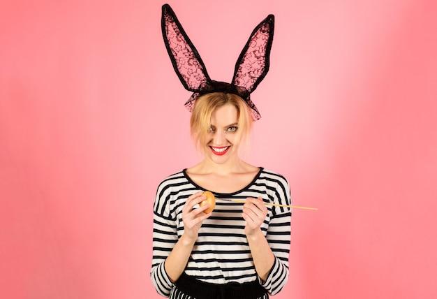 Gelukkig pasen. vrouw die in konijntjesoren ei, grappig konijn schilderen. voorjaarsvakantie.