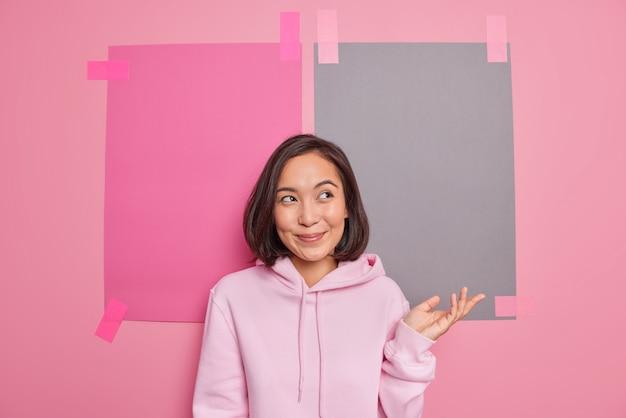 Gelukkig peinzende jonge aziatische vrouw heft handpalm op, ondervraagd, verbaasd om te antwoorden kreeg onverwachte suggestie-houdingen