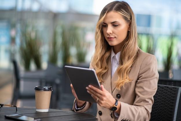 Gelukkig peinzende vrouw denken in een coffeeshop terras in de straat tijdens het gebruik van een tablet