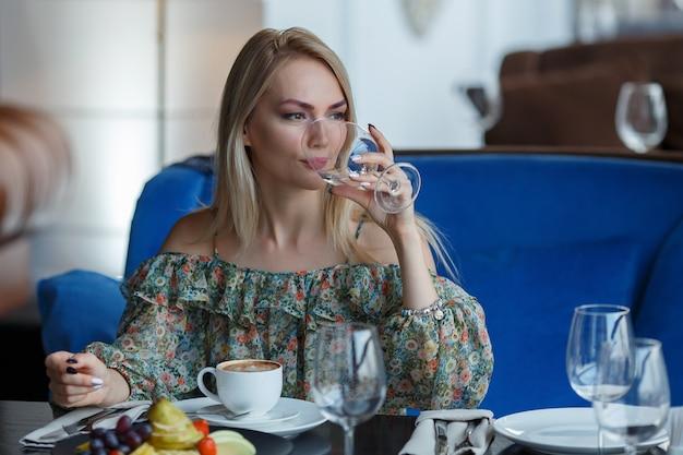 Gelukkig peinzende vrouw denken in restaurant met een glas in handen.