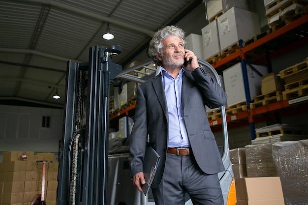Gelukkig peinzende zakenman permanent in de buurt van heftruck in magazijn en praten op mobiele telefoon. planken met goederen op achtergrond. bedrijfs- of logistiek concept