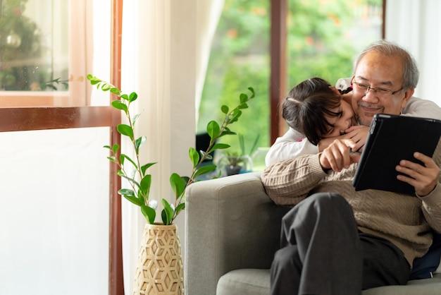 Gelukkig pensioen oudere man zittend op de bank in de woonkamer met kleindochter samen met behulp van digitale tablet.