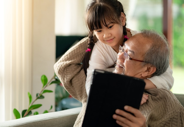 Gelukkig pensioen oudere man zittend op de bank met kleindochter samen