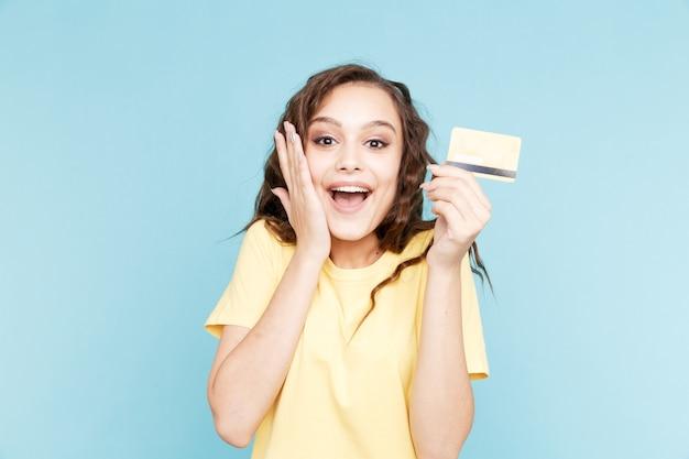 Gelukkig persoon met creditcard geïsoleerd in de blauwe studio.