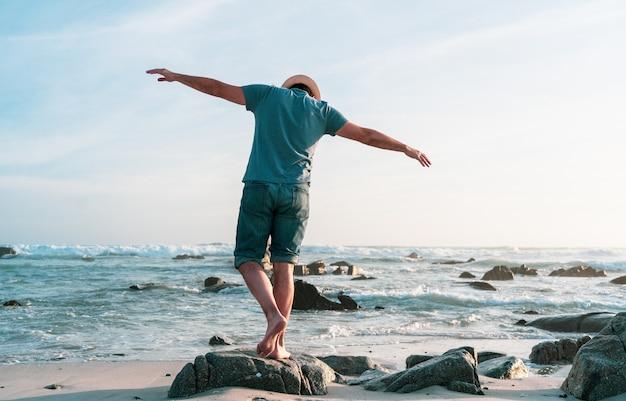 Gelukkig persoon met open armen op het strand bij zonsondergang
