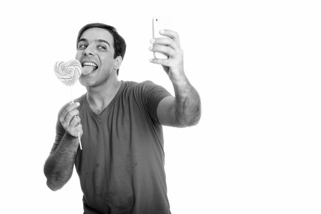 Gelukkig perzische man glimlachend en selfie foto met mobiele telefoon terwijl het likken van hartvormige lolly