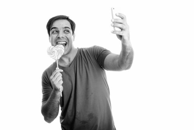 Gelukkig perzische man glimlachend en selfie foto met mobiele telefoon tijdens het eten van hartvormige lolly
