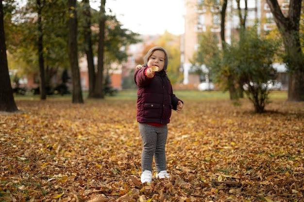 Gelukkig peuter kind speelt met gele bladeren op zonnige herfstdag.