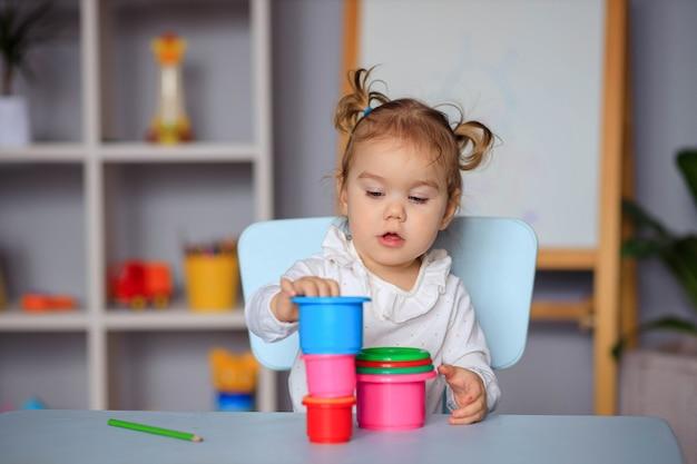 Gelukkig peuter meisje spelen aan de tafel