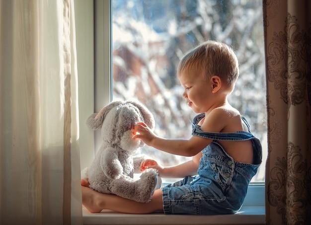 Gelukkig peuter spelen met een zacht stuk speelgoed op het raam