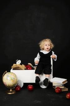 Gelukkig peutermeisje dichtbij de kar met boeken, bol en klok op een zwarte achtergrond