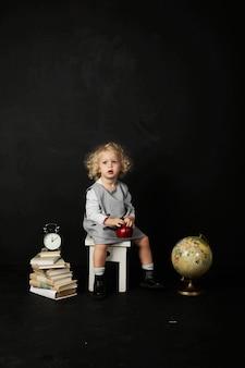 Gelukkig peutermeisje met boeken, bol en klok op een zwarte achtergrond