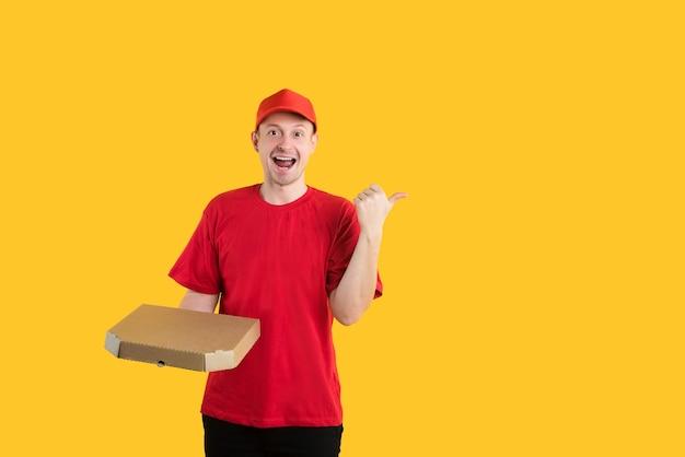 Gelukkig pizzabezorger in rood uniform op geel